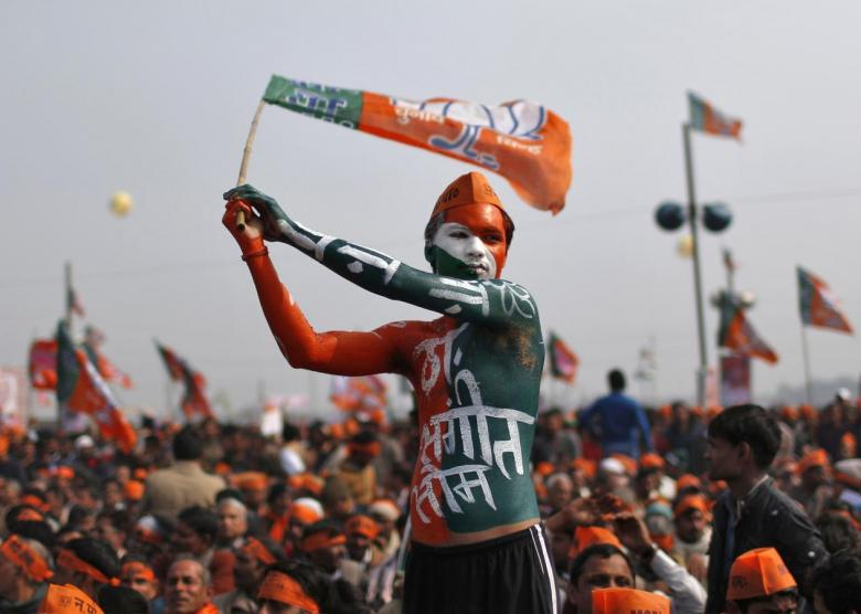 A supporter of India's main opposition Bharatiya Janata Party (BJP) waves the party's flag during a rally being addressed by Gujarat's Chief Minister and Hindu nationalist Narendra Modi, the prime ministerial candidate for BJP, ahead of the 2014 general elections, at Meerut in the northern Indian state of Uttar Pradesh February 2, 2014. REUTERS/Ahmad Masood (INDIA - Tags: POLITICS ELECTIONS)
