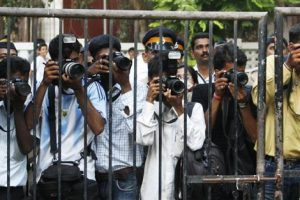 Indian press photographers stand behind a fence for security reasons as they take pictures of Belgium's Queen Paola in a school in Mumbai November 6, 2008. Belgium's King Albert II and Queen Paola are on a official state visit to India.     REUTERS/Francois Lenoir   (INDIA)