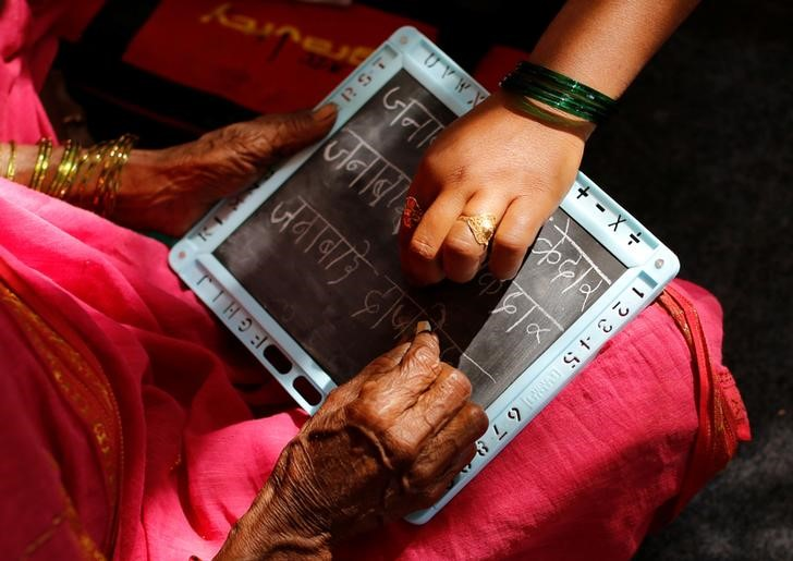Sheetal Prakash More (R), a 30-year-old teacher, helps Janabai Kedar, 74, as she writes on a slate at Aajibaichi Shaala (Grandmothers' School) in Fangane village, India, February 15, 2017. REUTERS/Danish Siddiqui