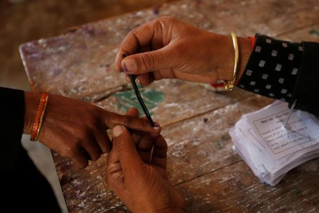 A woman gets her finger inked before casting her vote at a polling station during the state assembly election in Hapur, in the central state of Uttar Pradesh, India, February 11, 2017. REUTERS/Adnan Abidi