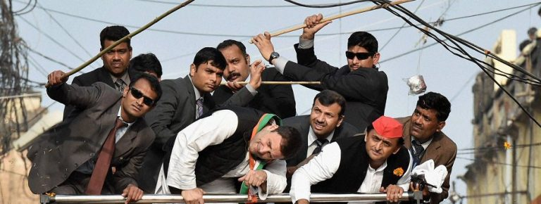 Lucknow : Security persons pushing away elctric cables above Uttar Pradesh Chief Minister and Samajwadi Party President Akhilesh Yadav and Congress Vice President Rahul Gandhi as they duck to avoid them during a road show in Lucknow on Sunday. PTI Photo by Nand Kumar (PTI1_29_2017_000224B)
