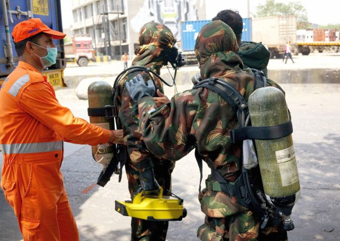 New Delhi: Members of National Disaster Response Force (NDRF) during the clean-up operation at a container depot, where a gas leak occurred, in New Delhi on Saturday. Nearly 200 girls from a school in southeast Delhi's Tughlakabad area were hospitalised after they complained of nausea and irritation in eyes. PTI Photo (PTI5_6_2017_000034B)