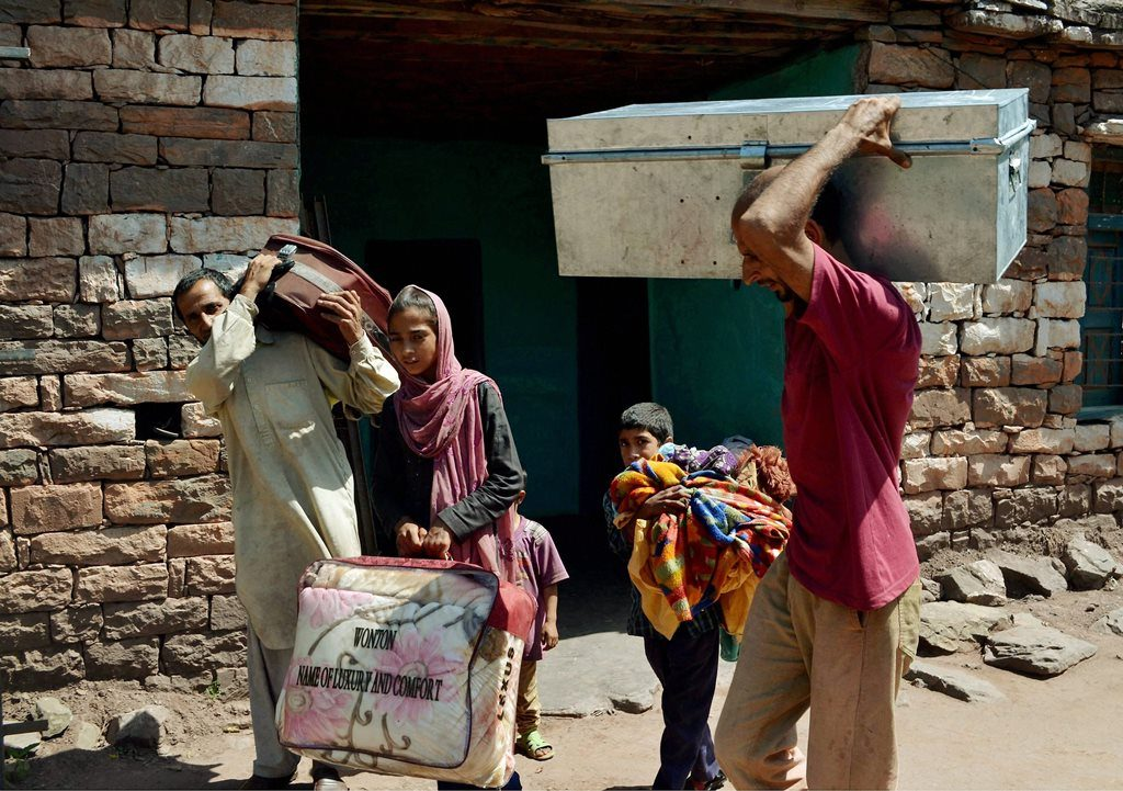 Villagers move with their belongings to a safer place after heavy shelling from Pakistan side along the line of control in Rajouri district in Jammu on Saturday. PTI