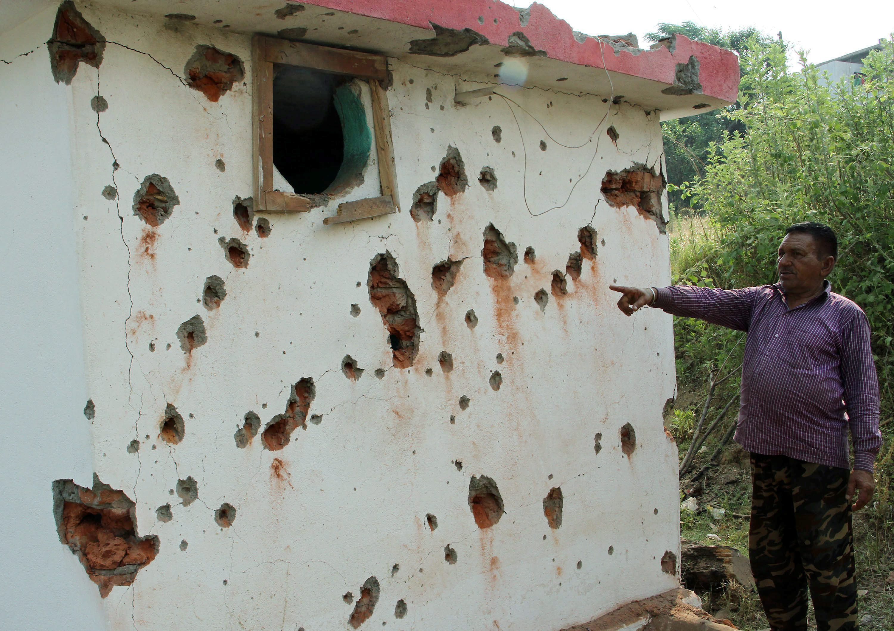 Jammu: A villagers  points out damaged wall of a house after mortal shelling from Pakistan, at Jhanghar village area near the Line of Control (LoC) at Nowshera sector 145km about from Jammu on Sunday. PTI Photo(PTI5_14_2017_000044B)