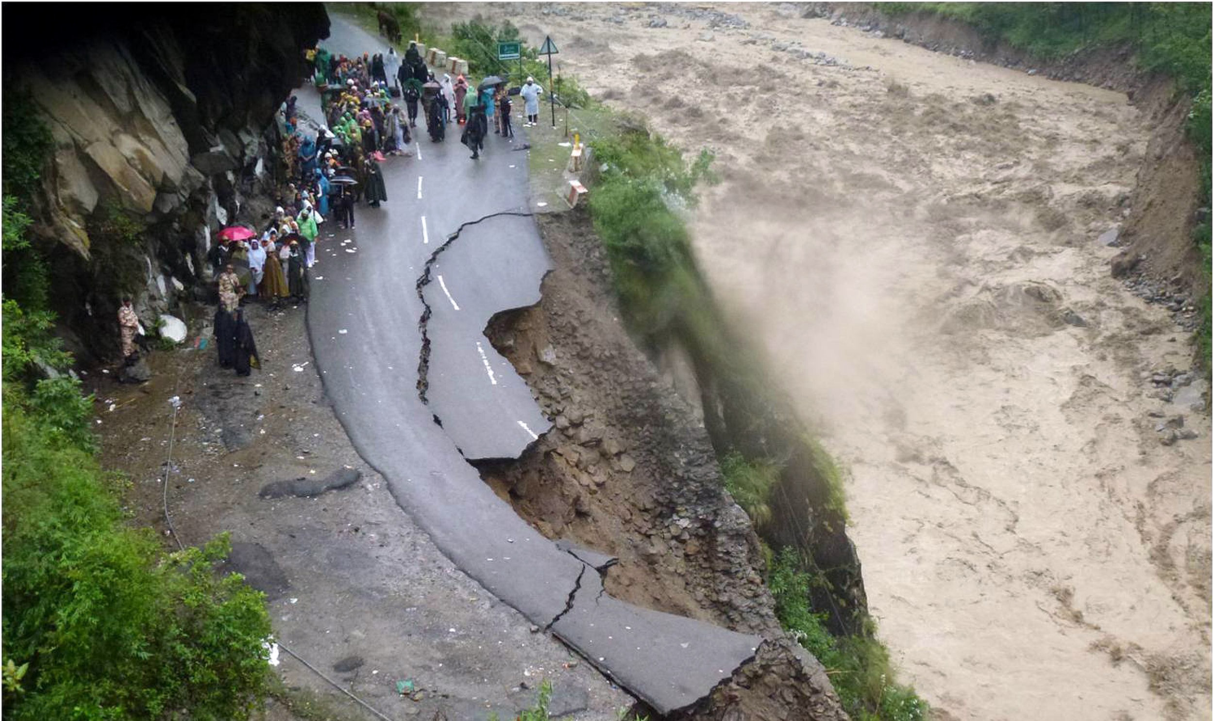 """In this handout photograph released by The Indian Army on June 18, 2013, Indian security personnel supervise residents and travellers as they stand on the remains of a flood damaged road alongside the River Alaknanda in Chamoli district in the northern Indian state of Uttarakhand on June 18, 2013. Torrential rains and flash floods washed away homes and roads in north India, leaving at least feared 60 people dead and thousands stranded, as the annual monsoon hit the country earlier than normal, officials said. Authorities called in military helicopters to try to rescue residents and pilgrims cut off by rising rivers and landslides triggered by more than three days of rain in the Himalayan state of Uttarakhand, officials said. -----EDITORS NOTE---- RESTRICTED TO EDITORIAL USE - MANDATORY CREDIT """"AFP PHOTO / INDIAN ARMY"""" - NO MARKETING NO ADVERTISING CAMPAIGNS - DISTRIBUTED AS A SERVICE TO CLIENTS"""