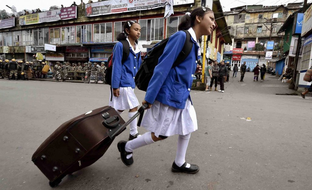Darjeeling: School students walk past as security personnel guarding in a street during GJM indefinite strike in Darjeeling on Wednesday. PTI Photo by Ashok Bhaumik (PTI6_21_2017_000358A)