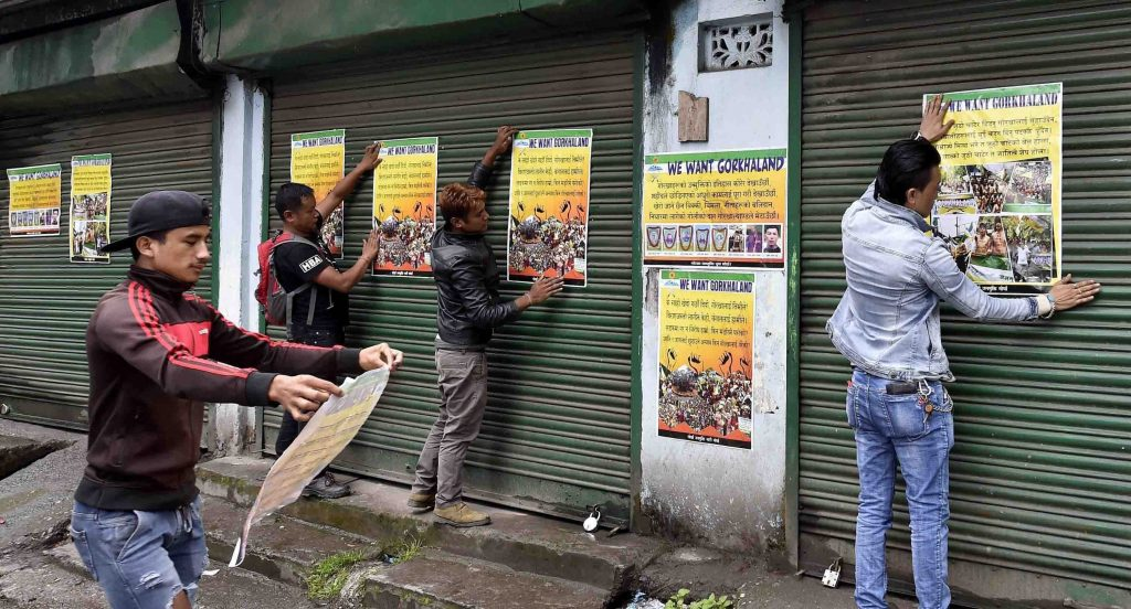 Darjeeling: Activists of GJM paste the party posters on the shutters of close shops during GJM indefinite strike near DM office in Darjeeling on Wednesday. PTI Photo by Ashok Bhaumik (PTI6_21_2017_000360B)