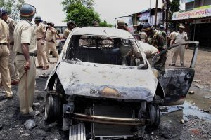 Mumbai : Police personnel inspect a charred vehicle that  was set ablaze by the farmers in Nevali during a violent protest against a proposed international airport on the outskirts of Mumbai on Thursday.  At least 25 people including policemen, locals and media persons were injured in the violence. PTI Photo  (PTI6_22_2017_000080B)