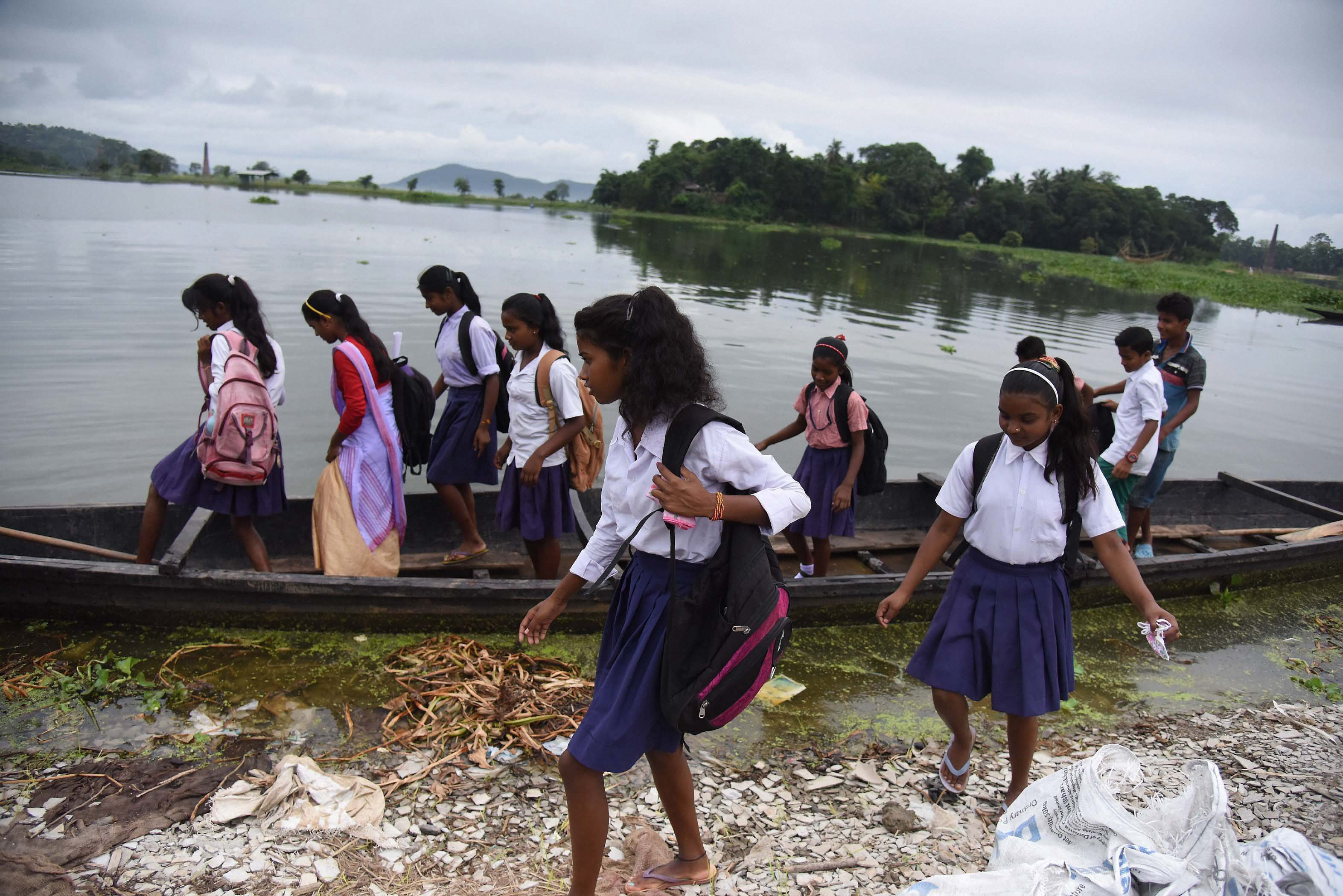 Guwahati: School girls travel cross a flooded area by boat at Rajbari village on the ourskirts of Guwahati on Saturday. PTI Photo(PTI7_1_2017_000154B)