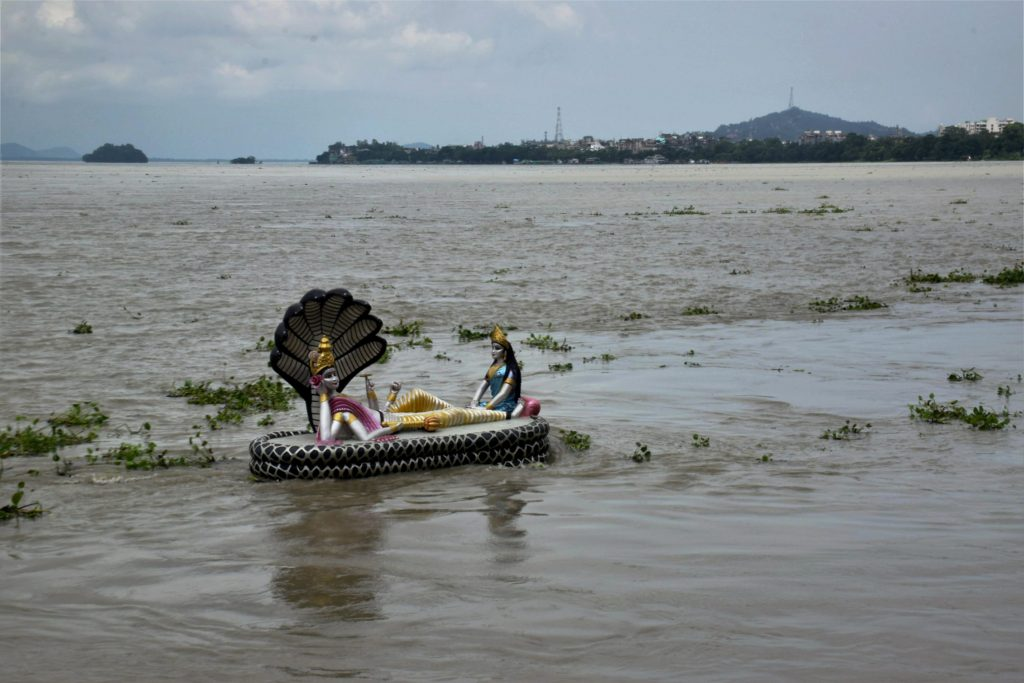 Guwahati: The water level of the flooded Brahmaputra River rises to the level of the statue of Lord Vishnu and Goddess Laxmi on the bank of the river near Chakreshwar Devalaya in Guwahati on Friday. PTI Photo (PTI7_7_2017_000157A)