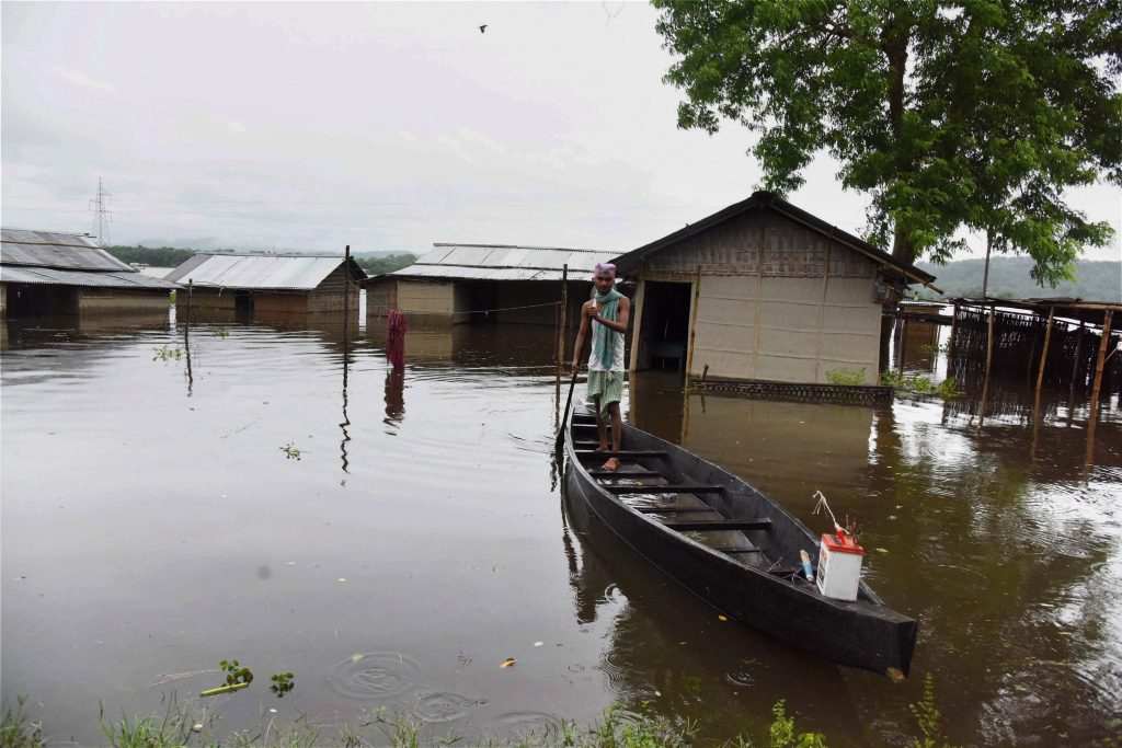Kaziranga: A man sails his boat in the flood-affected Kuthori village near Kaziranga National Park in Nagaon district of Assam on Monday. PTI Photo (PTI7_10_2017_000149A)