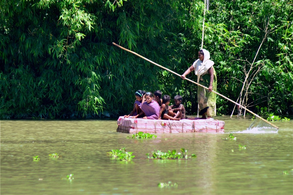 Kamrup: A woman with her children rows a makeshift raft across flood waters in the Kamrup district of Assam on Friday. PTI Photo (PTI7_14_2017_000217B)