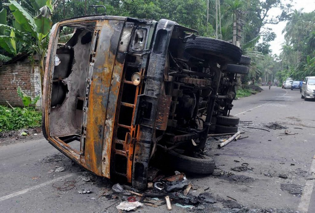 Baduria: A burnt vehicle seen at a road after a communal riot at Baduria in North 24 Pargana district of West Bengal on Wednesday. PTI Photo (PTI7_5_2017_000228B)