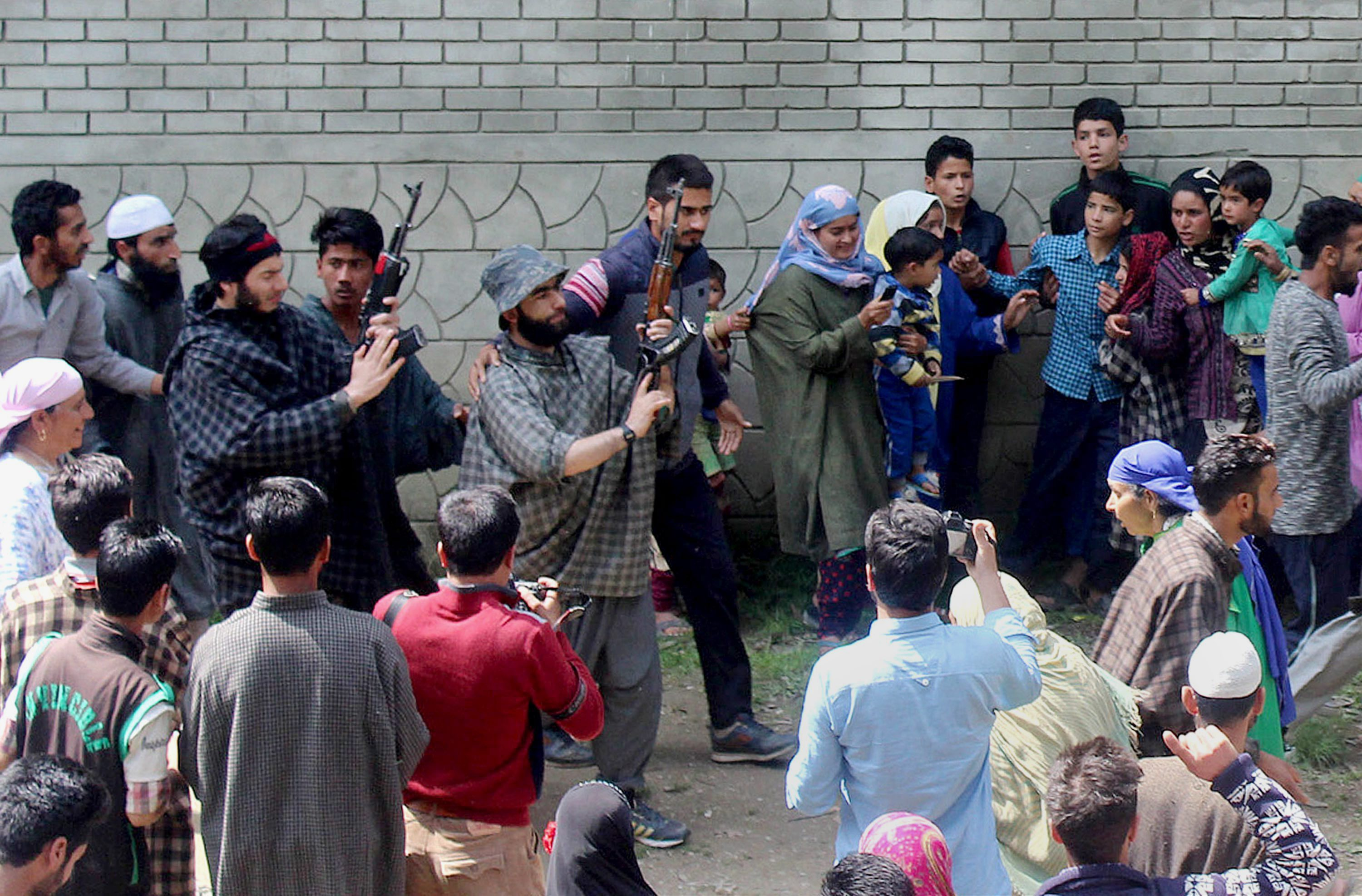 Kulgam: Suspected militants brandish their guns and shout slogans at the funeral of a slain colleague, killed in a shootout with the police, at Qoimoh in Kulgam district of south Kashmir on Sunday. PTI Photo (PTI5_7_2017_000188B)