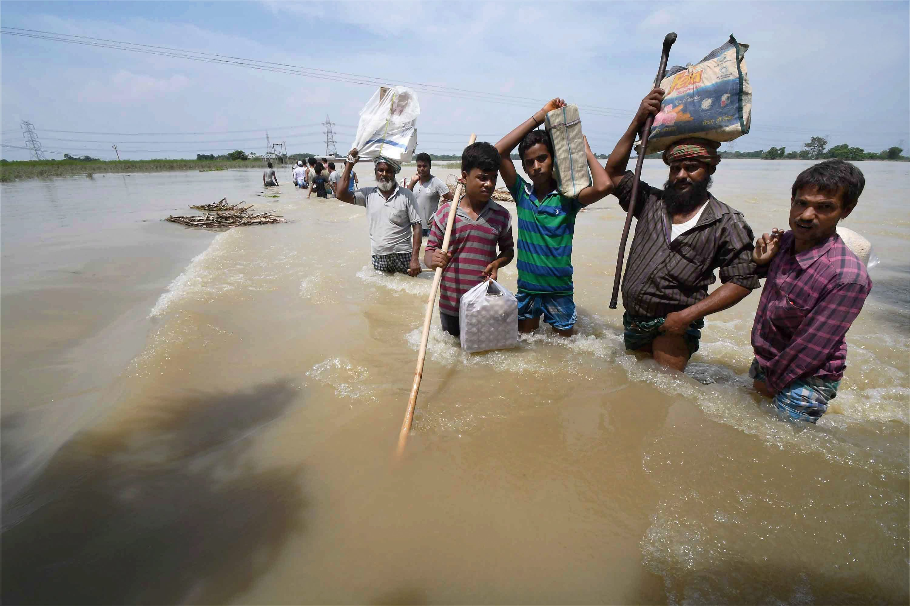 Purnea: Flood-affected villagers shift with their belongings in Purnea district on Tuesday. PTI Photo (PTI8_15_2017_000194B)