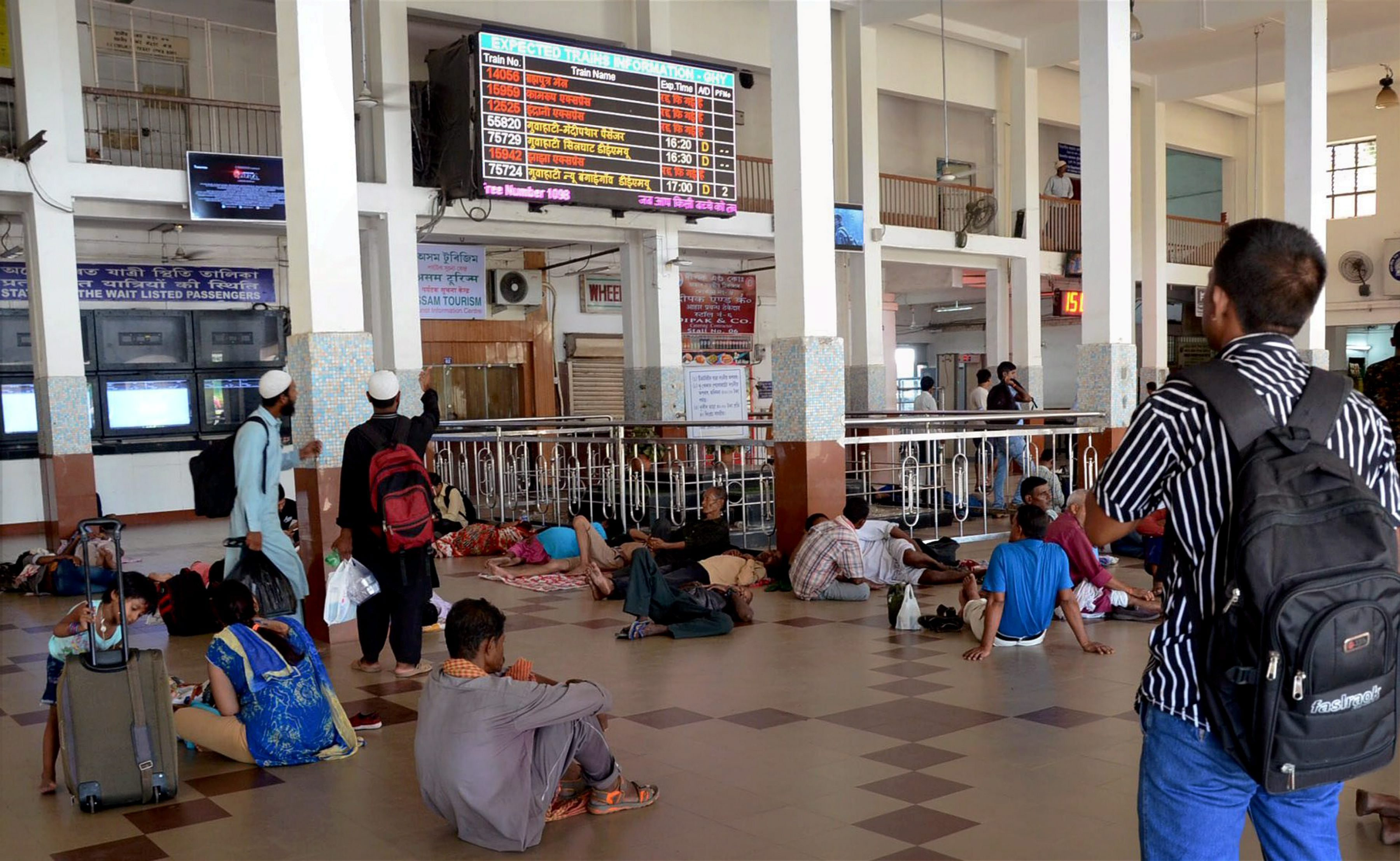 Guwahati: Passengers looking at the screen displaying the schedules of the trains at Guwahati Railway Station on Thursday: Major trains were cancelled due to floods in Assam. PTI Photo (PTI8_17_2017_000138B)