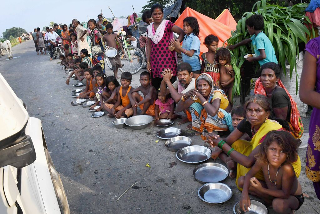 Motihari: Flood-affected people, sheltering along a road, wait for food in Motihari district of Bihar on Thursday. PTI Photo (PTI8 17 2017 000167B)