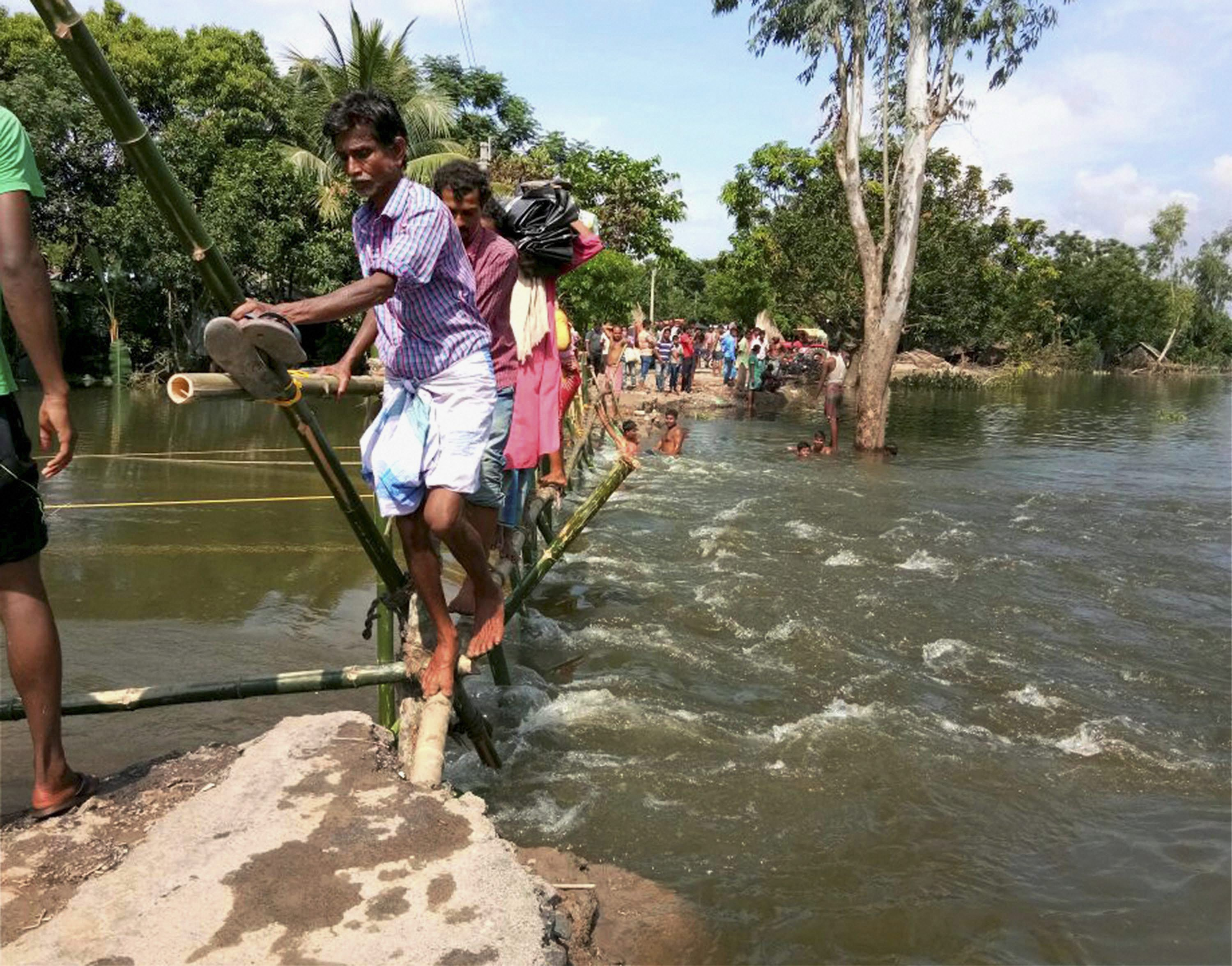 North Dinajpur: Villagers use a makeshift bamboo bridge to cross a flooded locality at Itahar village in North Dinajpur district of West Bengal on Sunday. PTI Photo (PTI8_21_2017_000113B)