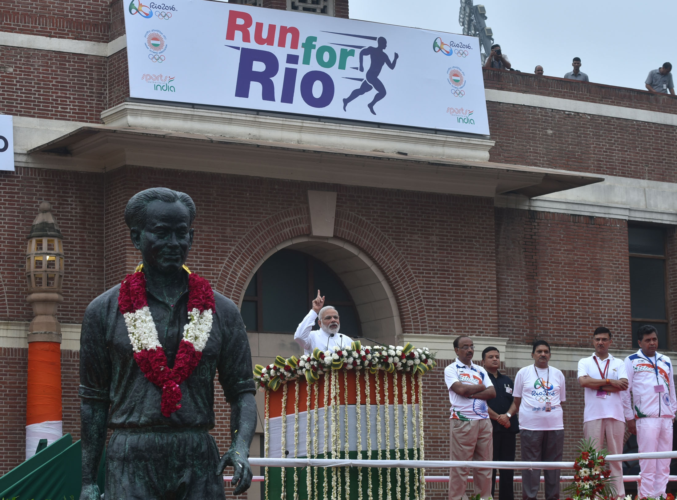 """The Prime Minister, Shri Narendra Modi addressing at the flagging off ceremony of """"Run For Rio"""", at Major Dhyan Chand National Stadium, in New Delhi on July 31, 2016. The Minister of State for Youth Affairs and Sports (I/C), Water Resources, River Development and Ganga Rejuvenation, Shri Vijay Goel and the Secretary, Ministry of Youth & Sports, Shri Rajiv Yadav are also seen."""