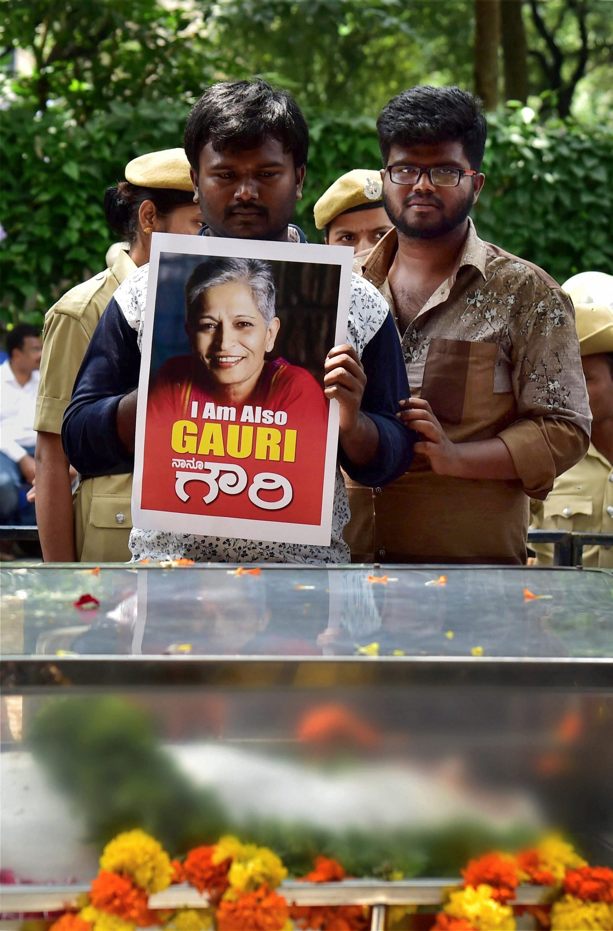Bengaluru: A supporter displays a poster near the mortal ramains of journalist Gauri Lankesh, who was shot dead by miscreants at her residence last night, in Bengaluru on Wednesday. PTI Photo by Shailendra Bhojak(PTI9_6_2017_000085B)