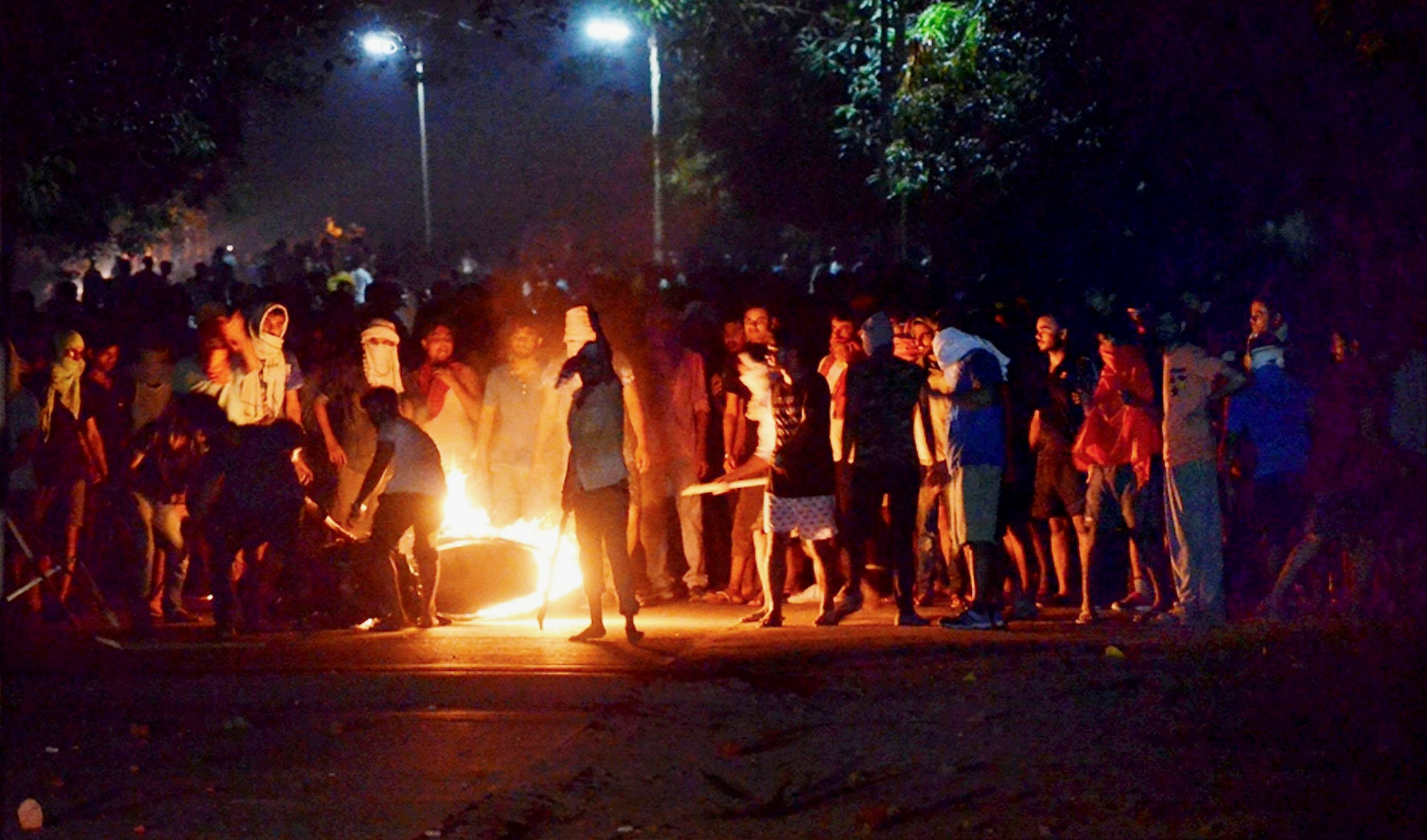 Varanasi: A bike in flames during clashes between the students and police at Banaras Hindu University in Varanasi, late Saturday night. Female students at the prestigious University were protesting against the administration's alleged victim-shaming after one of them reported an incident of molestation on Thursday. PTI Photo (PTI9_24_2017_000080A)