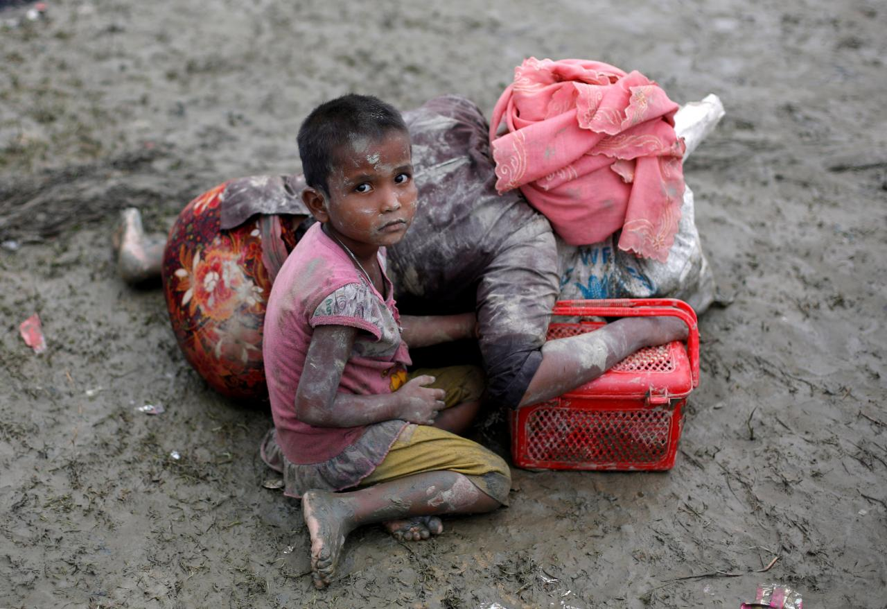 A Rohingya refugee girl sits next to her mother who rests after crossing the Bangladesh-Myanmar border, in Teknaf, Bangladesh, September 6, 2017. REUTERS/Danish Siddiqui