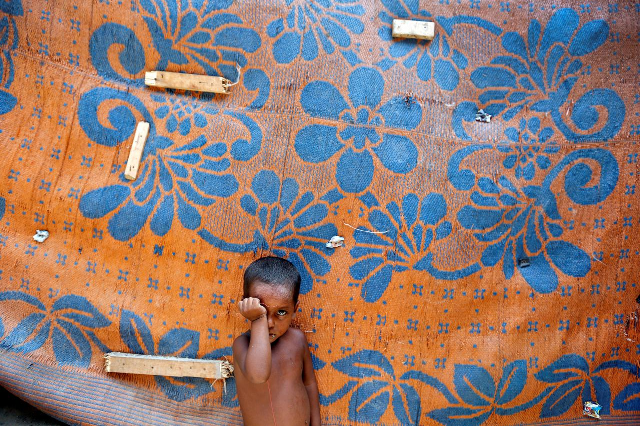 FILE PHOTO: A boy from the Rohingya community stands outside a shack at a camp in Delhi, India August 17, 2017. REUTERS/Cathal McNaughton/File photo