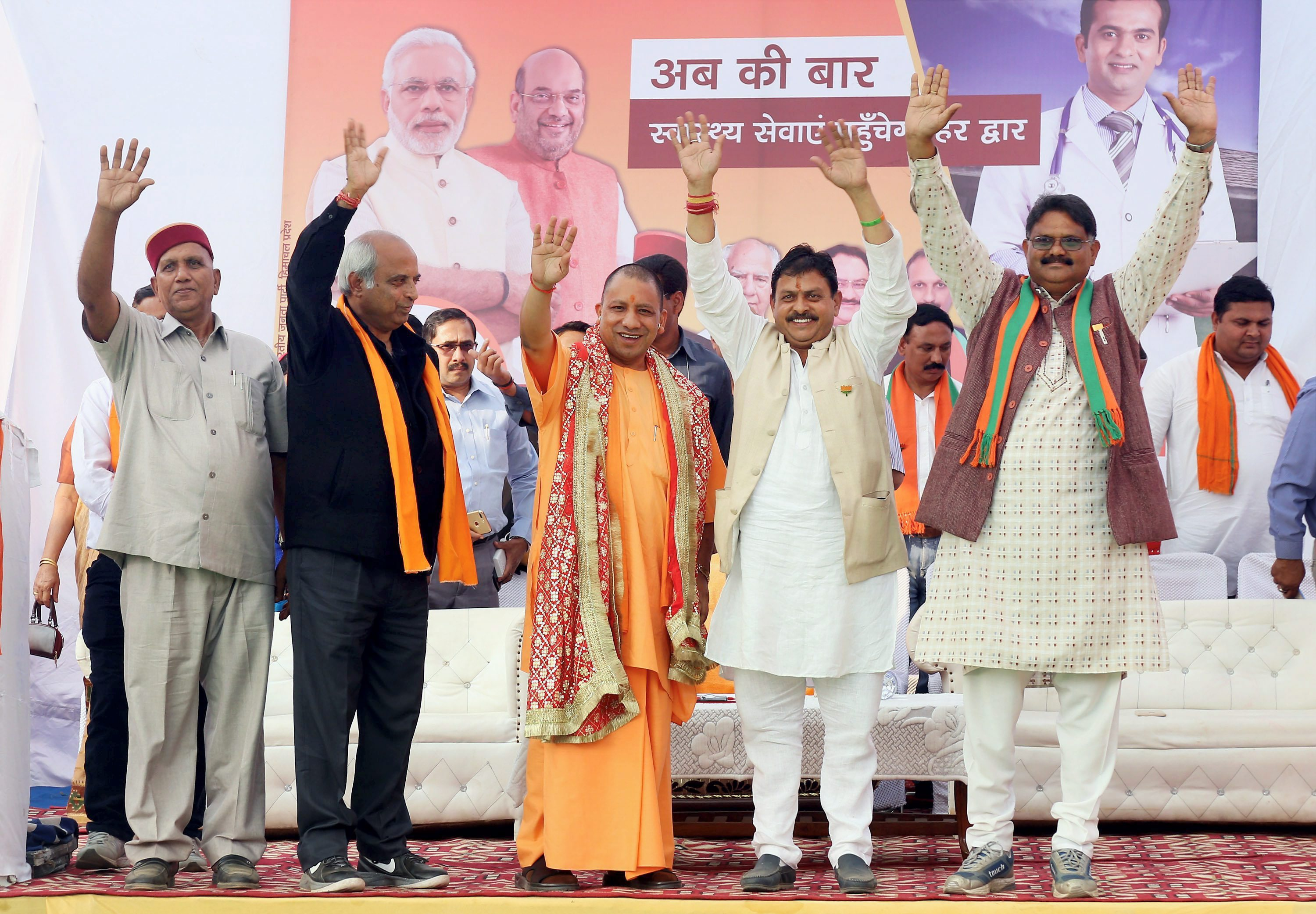 Dharamsala : BJP workers welcome Uttar Pradesh Chief Minister Yogi Adityanath during an election rally while campaigning for party candidate Arun Kumar (Kukka) from Nagrota Bagwan in Dharamsala on Monday. PTI Photo (PTI10_30_2017_000163B)