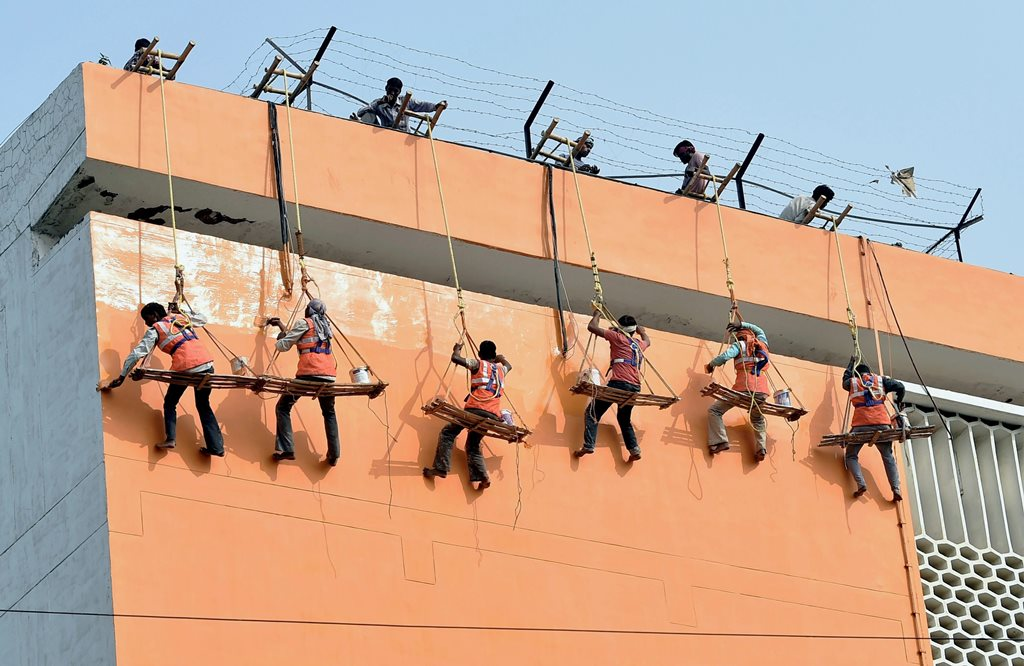 Lucknow: Workers paint the Secretariat Annexe building in saffro in Lucknow on Tuesday. PTI Photo by Nand Kumar(PTI10 31 2017 000140B)