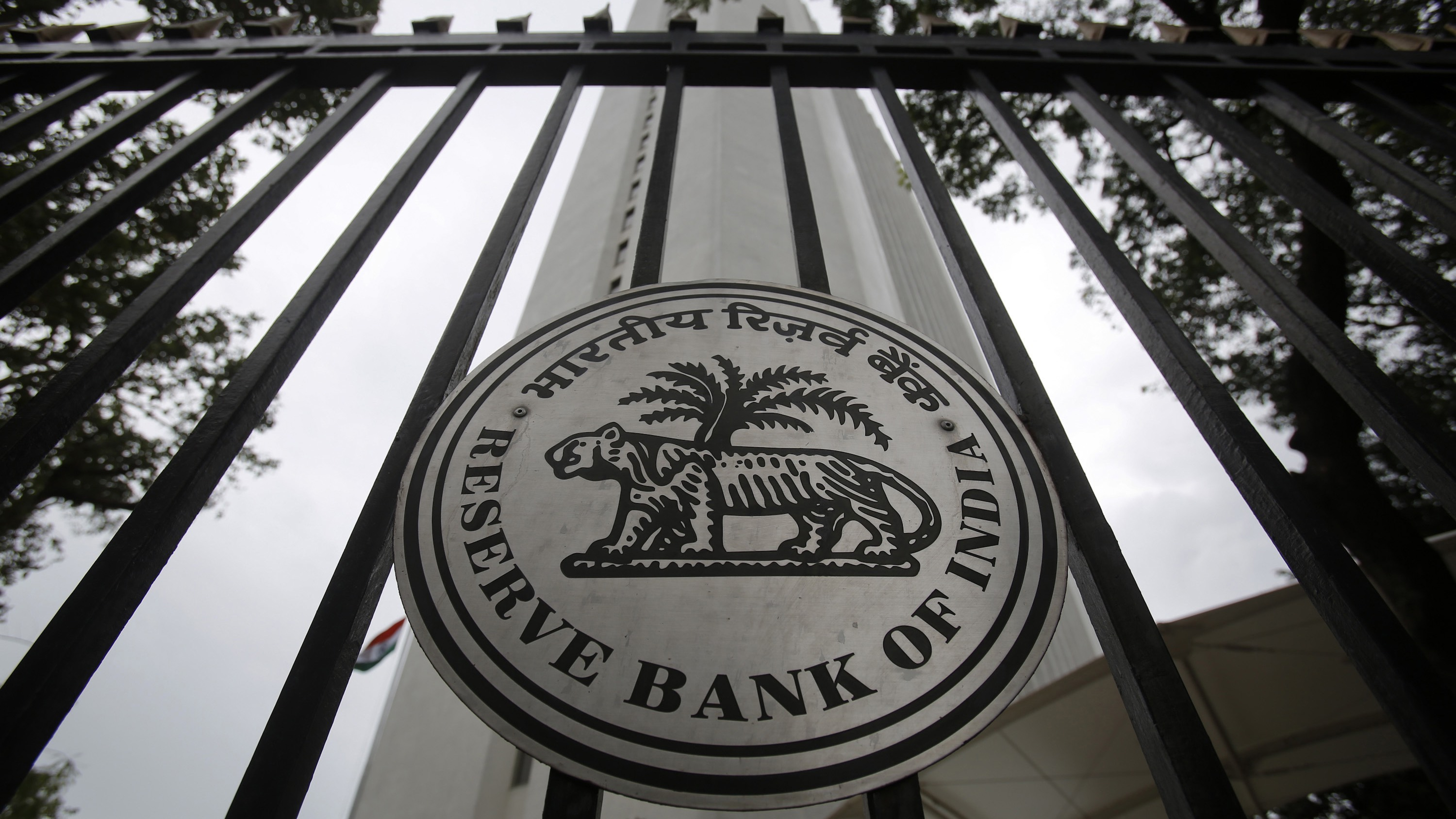 The Reserve Bank of India (RBI) seal is pictured on a gate outside the RBI headquarters in Mumbai July 30, 2013. India's central bank left interest rates unchanged on Tuesday as it supports a battered rupee but said it will roll back recent liquidity tightening measures when stability returns to the currency market, enabling it to resume supporting growth. REUTERS/Vivek Prakash (INDIA - Tags: BUSINESS LOGO) - RTX124GY