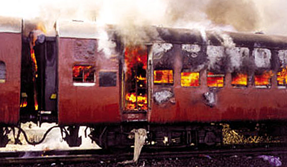 Smoke pours from the carriage of a train on fire in Godhra, in the western Indian state of Gujarat, February 27, 2002. Up to 56 people died on Wednesday after a train carrying Hindu activists from the controversial site of a razed mosque was set on fire in western India, officials said. REUTERS/Str BEST QUALITY AVAILABLE REUTERS JSG/AA - RTRTH35