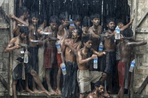 Migrants, who were found at sea on a boat, collect rainwater during a heavy rain fall at a temporary refugee camp near Kanyin Chaung jetty, outside Maungdaw township, northern Rakhine state, Myanmar June 4, 2015. REUTERS/Soe Zeya Tun