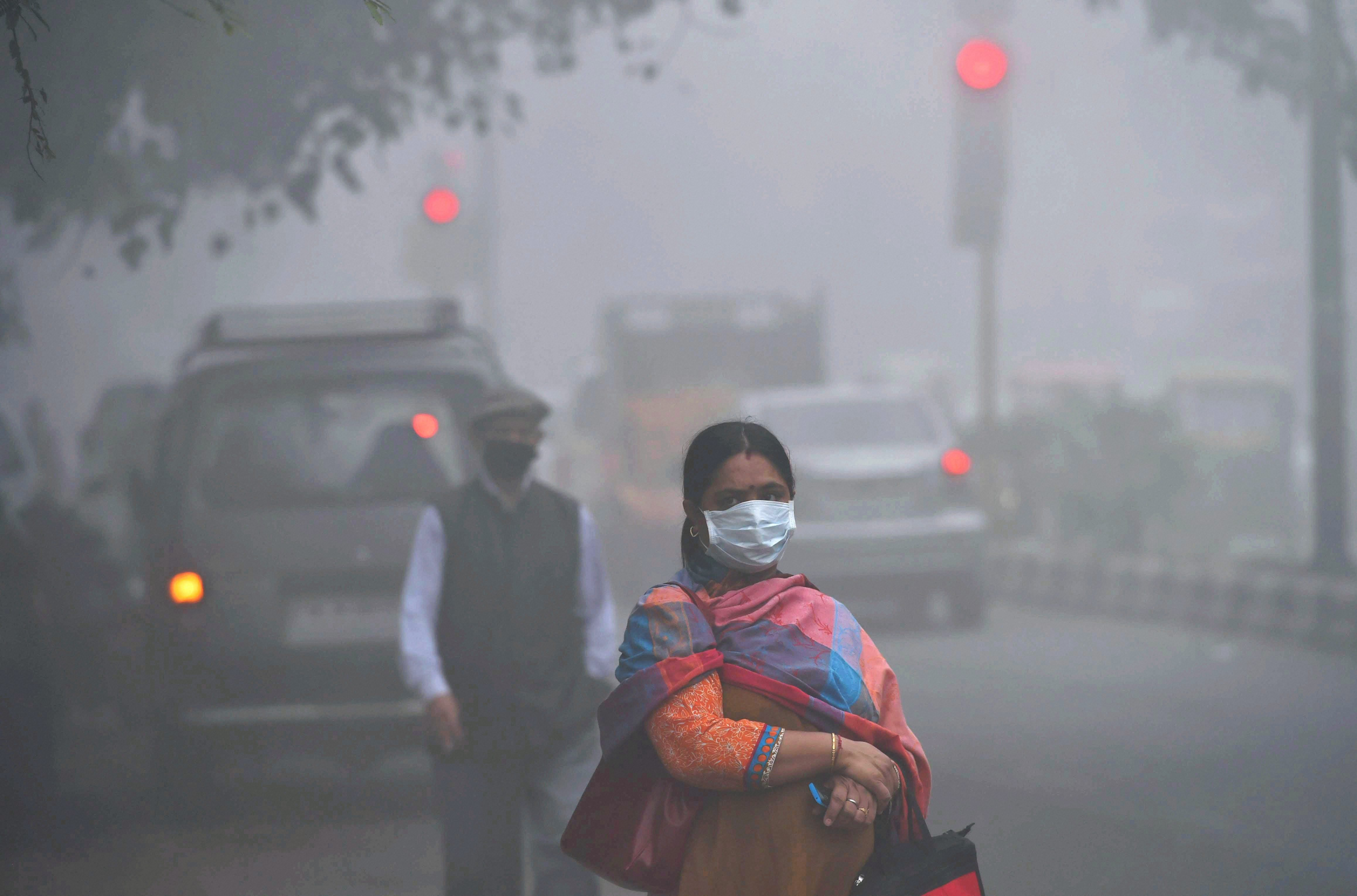 New Delhi: A woman wears an anti-pollution mask as smog covers the capital's skyline on Wednesday. Yesterday the air quality hit severe levels in New Delhi. PTI Photo by Shahbaz Khan(PTI11_8_2017_000013A)