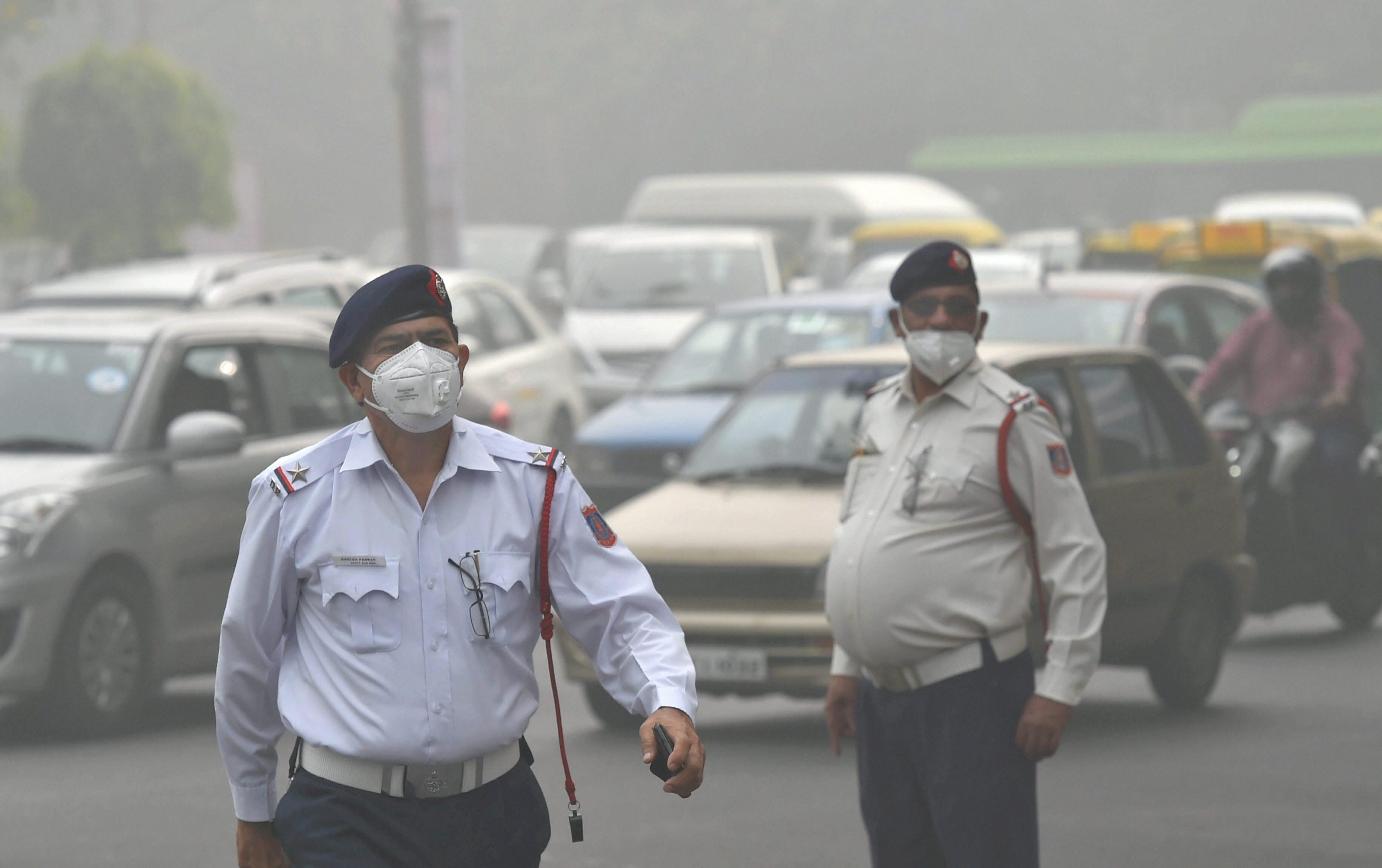 New Delhi: Traffic policemen wear masks to protect themselves from heavy smog and air pollution while manning the traffic, in New Delhi on Wednesday. The smog and air pollution continue to be above the severe levels in Delhi NCR on Tuesday. PTI Photo by Kamal Kishore(PTI11_8_2017_000037B)