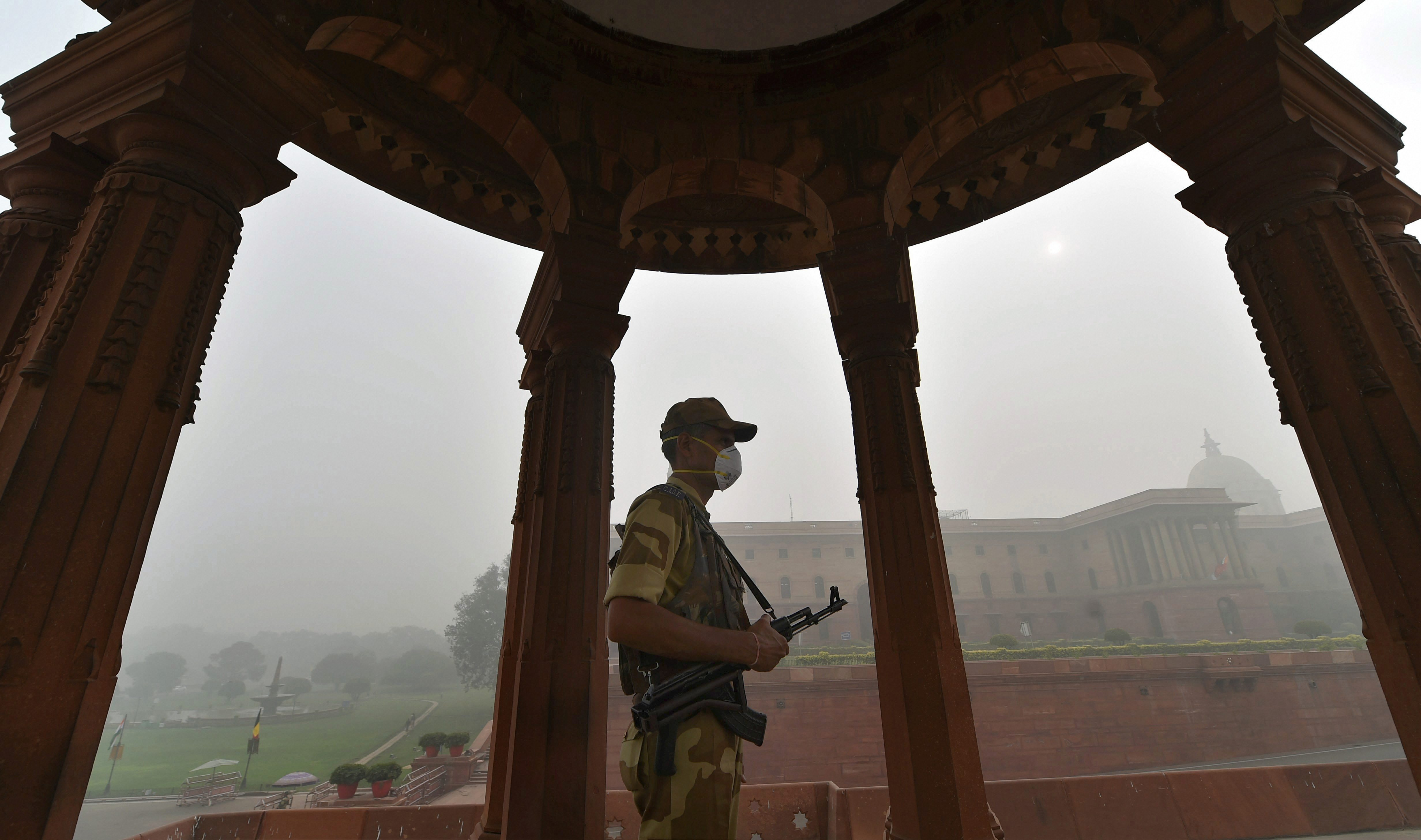 New Delhi: Security person wears mask to protect from heavy smog and air pollution at North Block in New Delhi on Wednesday. The smog and air pollution continue to be above the severe levels in Delhi NCR. PTI Photo by Vijay Verma(PTI11_8_2017_000088A)