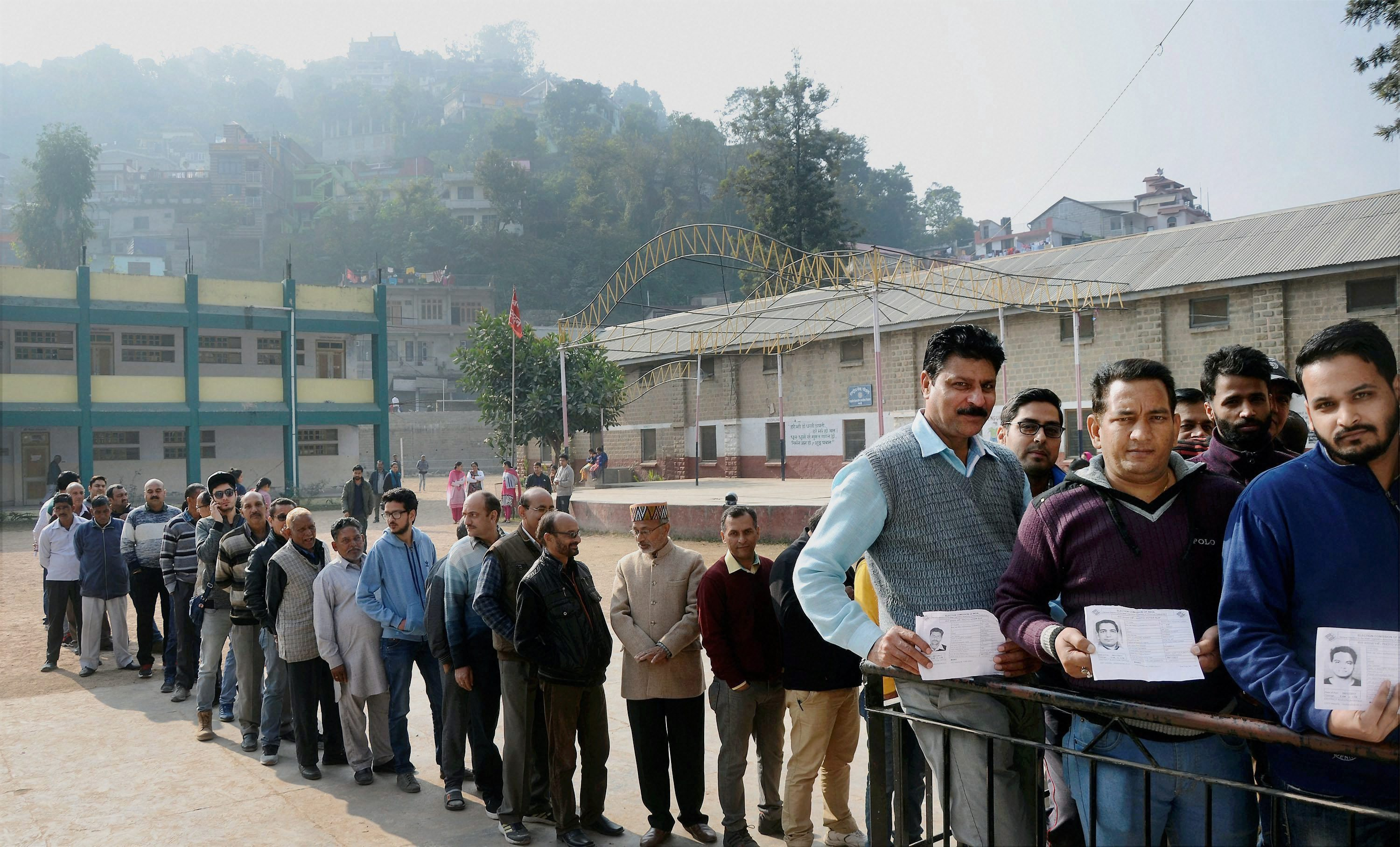 Mandi: Voters in a queue show their voter identity card at a polling booth in Mandi, Himachal Pradesh on Thursday. PTI Photo (PTI11_9_2017_000015B)