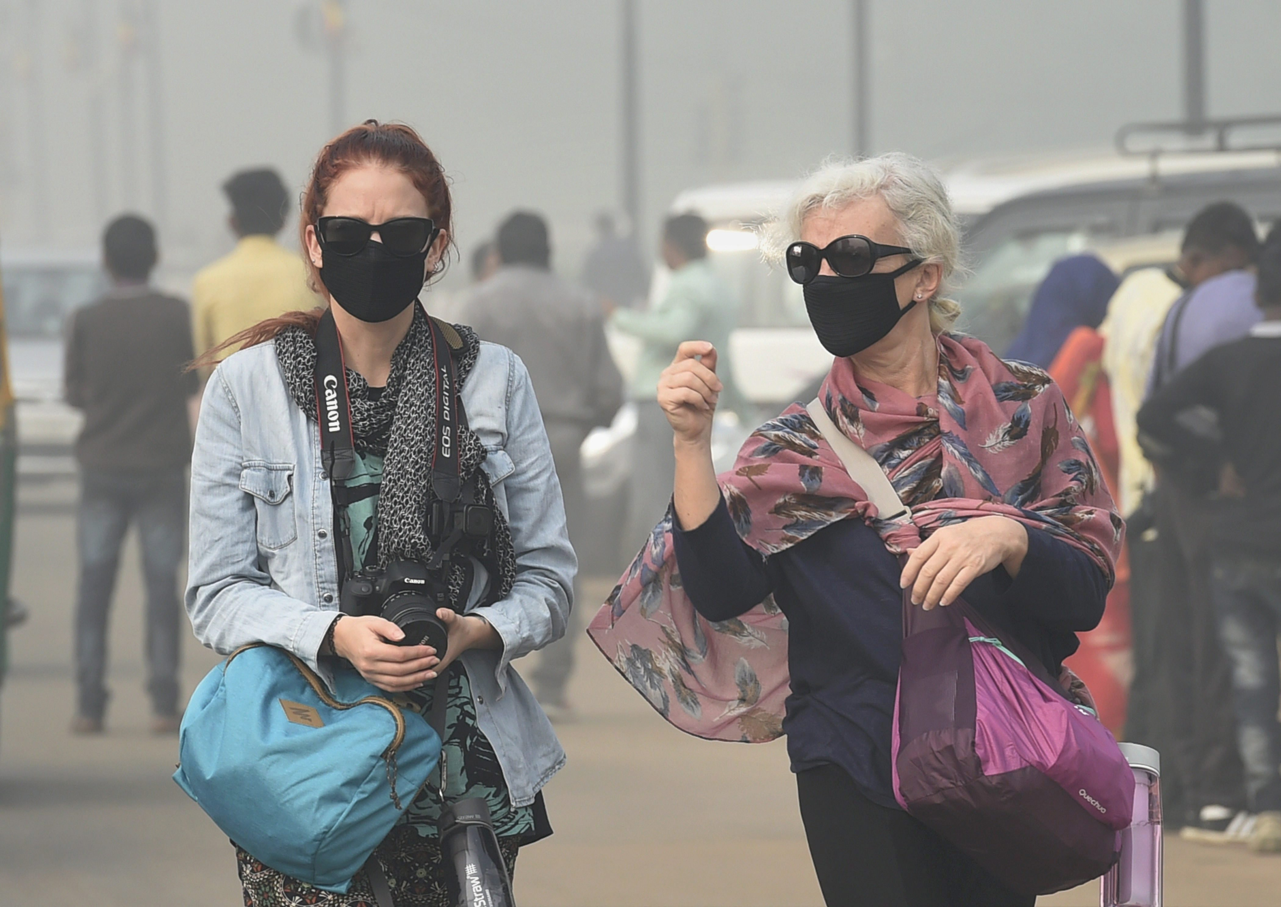 New Delhi: Foreign tourists wear masks to protect themselves from heavy smog and air pollution that reached high levels at Rajpath, in New Delhi on Friday. PTI Photo by Kamal Singh(PTI11 10 2017 000033A)