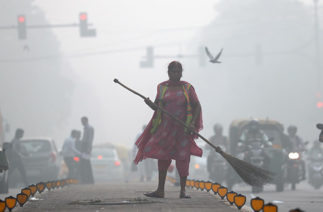 A street cleaner works in heavy smog in Delhi, India, November 10, 2017. REUTERS/Cathal McNaughton