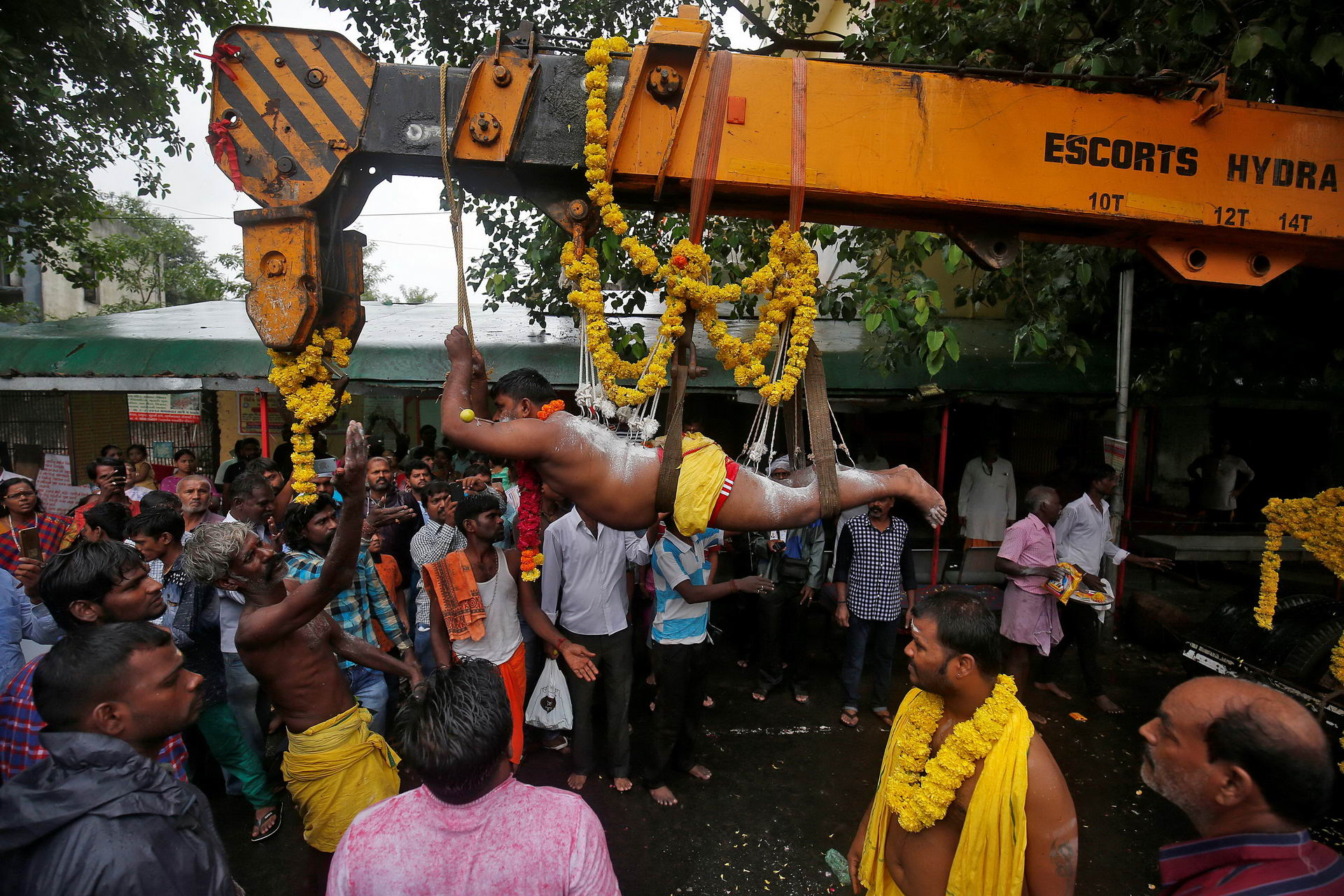 A Hindu devotee with his back and legs pierced with iron hooks suspends from a crane during an annual religious procession called Shitla Mata in Ahmedabad, India, July 23, 2017. (Photo by Amit Dave/Reuters)