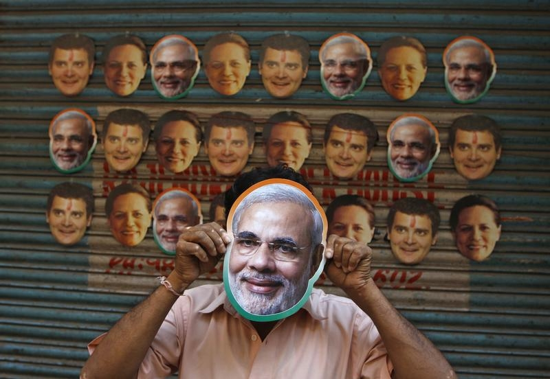 A vendor wears a mask of Hindu nationalist Narendra Modi, prime ministerial candidate for main opposition Bharatiya Janata Party (BJP) and Gujarat's chief minister, to attract customers at his stall selling masks of Indian political leaders ahead of general election in the southern Indian city of Chennai April 3, 2014. India, the world's largest democracy, will hold its general election in nine stages staggered between April 7 and May 12. REUTERS/Babu (INDIA - Tags: ELECTIONS POLITICS TPX IMAGES OF THE DAY) - RTR3JSS0