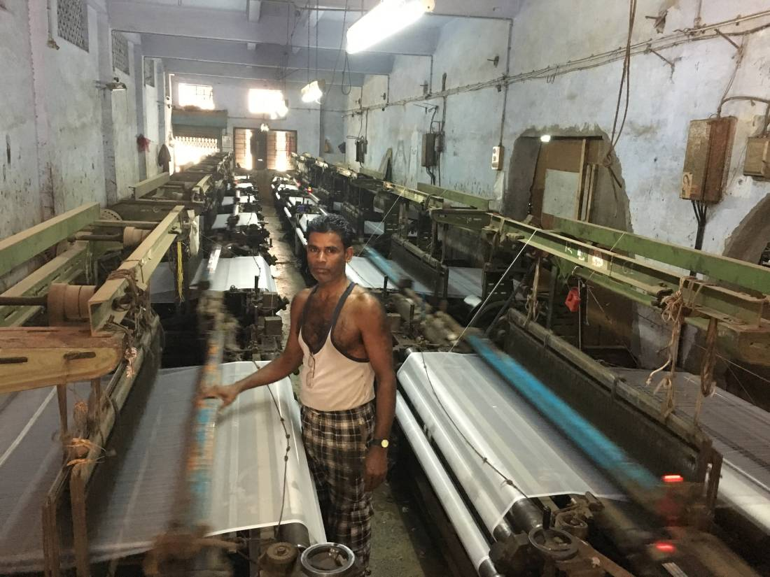 Vijay Pradhan, 45, attends to the 12 power looms that he operates at a synthetic textile unit in Surat, India's largest manufacturer of manmade fabric. THOMSON REUTERS FOUNDATION/Roli Srivastava