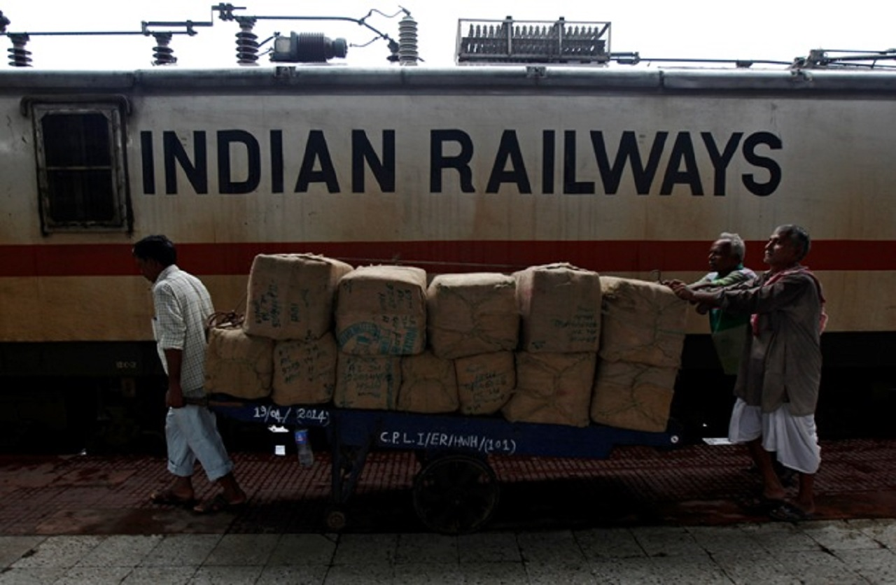Porters transport goods on a hand-pulled trolley to load onto a train at a railway station in Kolkata July 8, 2014.