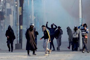 Srinagar: Protesters throw stones on security forces amid tear smoke during a protest against the alleged killing of two youth in Army firing in Shopian district of South Kashmir, in Srinagar on Sunday. PTI Photo by S Irfan    (PTI1_28_2018_000158B)