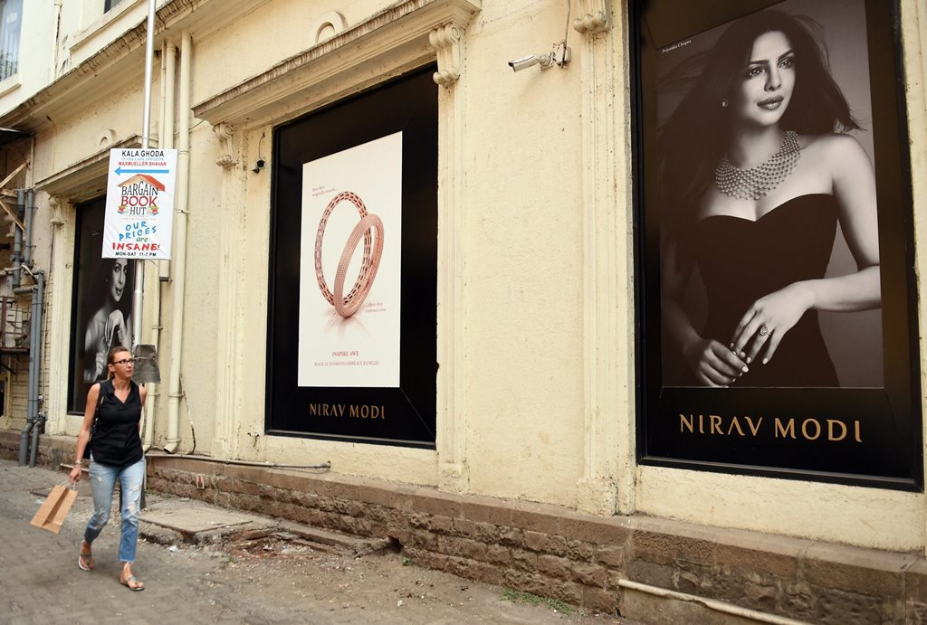 Mumbai: A woman walks near a Nirav Modi jewellery showroom at Kala Ghoda in Mumbai on Thursday. Enforcement Directorate is conducting searches at Nirav Modi's home, showrooms and offices in Mumbai, Delhi and Surat foillowing Punjab National Bank's (PNB) complaint of massive fraudulant transactions to benefit the celebrity jeweller. PTI Photo by Shashank Parade (PTI2_15_2018_000036B)