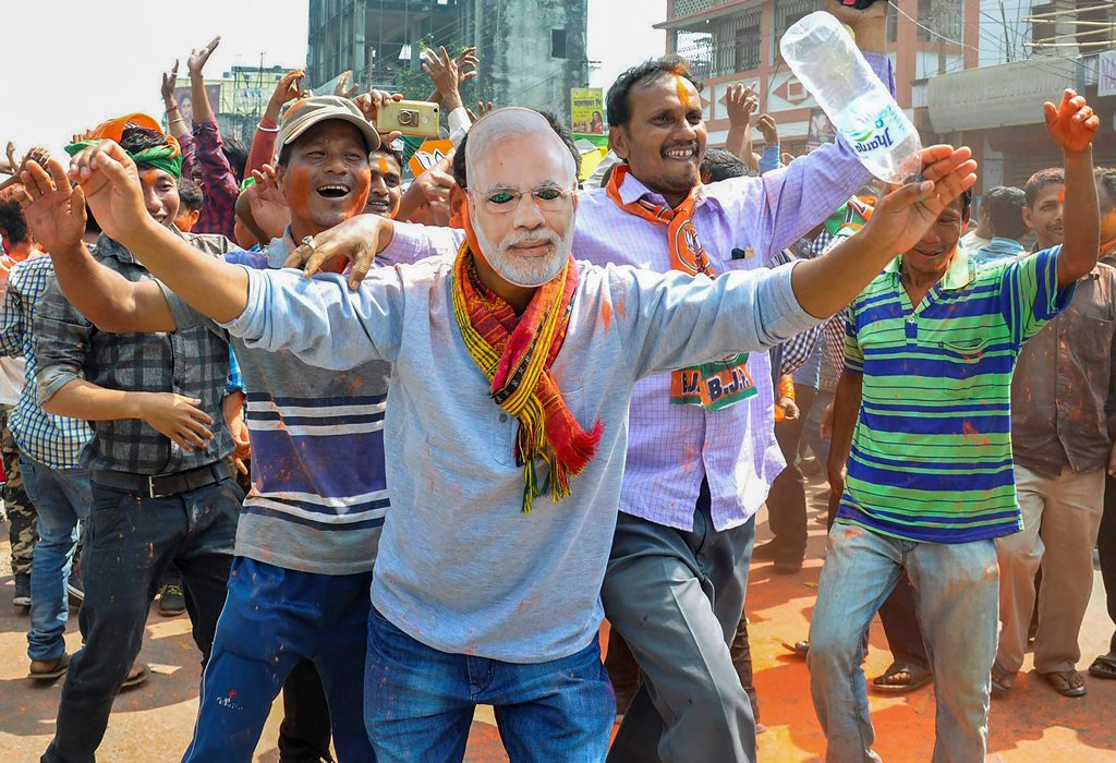 Agartala: A BJP supporters wear a mask of Prime Minister Narendra Modi to celebrate party's victory in Tripura Assembly elections in Agartala on Saturday. BJP's win marks an end to 25 years of CPI-M government rule in the state. PTI Photo (PTI3_3_2018_000094B)