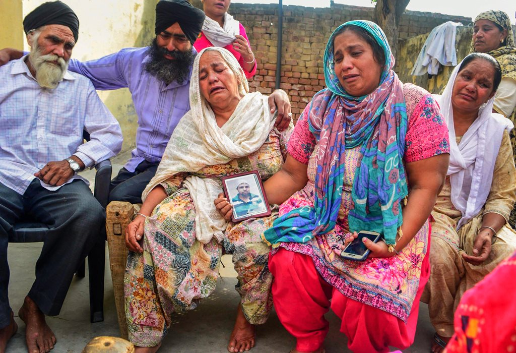 Amritsar: Family members grieve by a portrait of one of the 39 Indian workers feared killed in Iraq, on the outskirts of Amritsar on Tuesday. External Affairs Minister Sushma Swaraj in a statement made at Rajya Sabha today, stated that the 39 bodies exhumed from a mount in Badoosh in Iraq have been identified as those of abducted Indians and will be brought back to India on a special plane. PTI Photo(PTI3_20_2018_000158B)