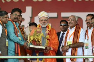 Bengaluru: Prime Minister Narendra Modi being presented a memento by BJP state leaders during the completion of the Parivartan Yatra rally in Bengaluru on Sunday. BJP State Unit President B. S. Yeddyurappa is also seen. PTI Photo by Shailendra Bhojak(PTI2_4_2018_000172B)