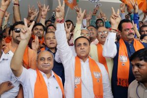 """Gandhinagar: Gujarat Chief Minister Vijay Rupani, deputy Chief Minister Nitin Patel, State President Jitu Vaghani and other BJP leaders show victor sign as they celebrate the party's performance in Karnataka Assembly elections, at the BJP office """"Kamalam"""" at Gandhinagar on Tuesday. PTI Photo (PTI5_15_2018_000073B)"""