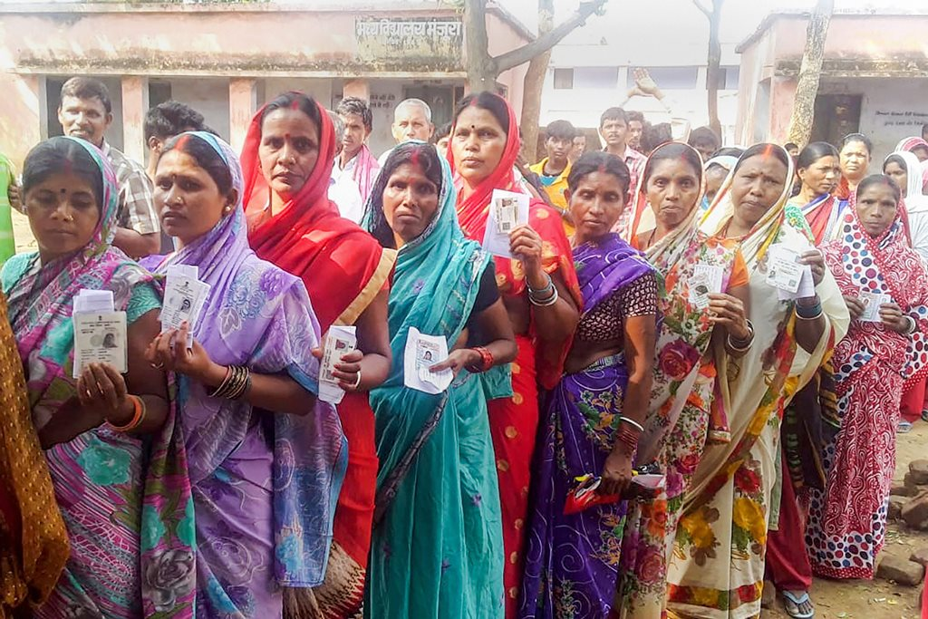 Gomia: Voters show their Election Commission cards as they queue to cast their vote at a polling station, during Gomia constituency Assembly by-election, at Gomia, on Monday, 28 May 2018. (PTI Photo) (PTI5_28_2018_000037B)