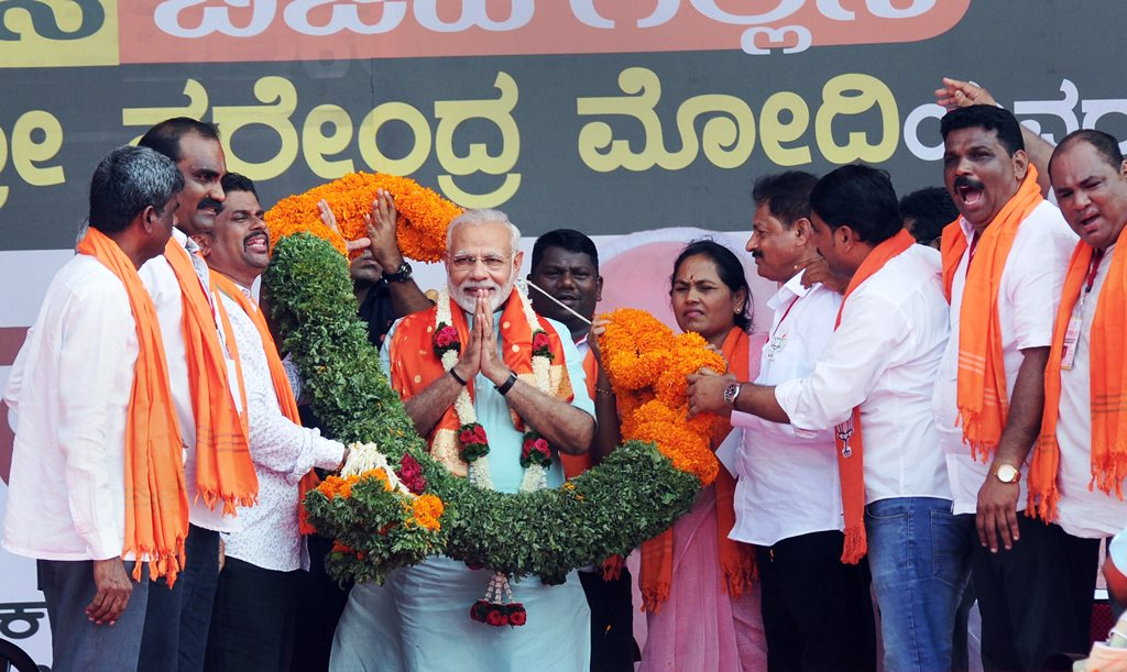 Udupi: Prime Minister Narendra Modi being garlanded by BJP workers at an election campaign rally ahead of Karnataka polls, in Udupi on Tuesday. PTI Photo